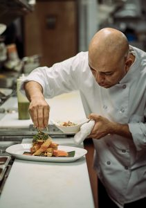 Chef Willi Linares plating a Yuca Frita.
